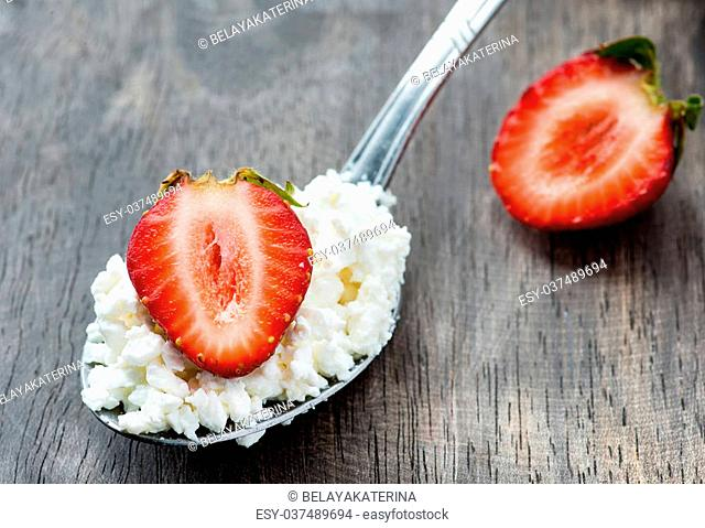 Strawberry and cottage cheese in spoon over wooden background, selective focus