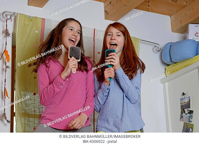 Girls, children singing into hairbrush as microphone, Germany