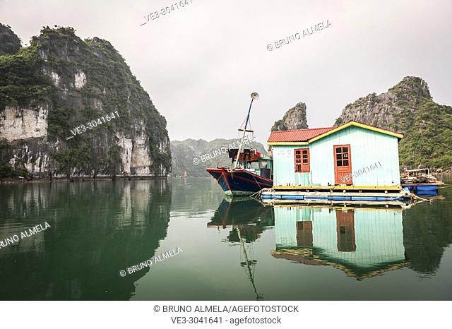 Fishing boat and traditional house in karst landscape of Ha Long Bay, Quang Ninh Province, Vietnam. Ha Long Bay is a UNESCO World Heritage Site