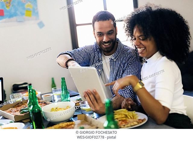 Happy couple sharing tablet at dining table