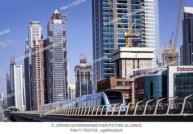 In Dubai, a metro train travels on a viaduct between skyscrapers. The metro has been part of the city since 2009. The ultra-modern trains run completely...