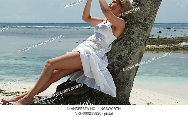 woman leaning against a palm tree in a white dress