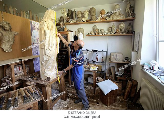 Sculptor measuring wooden figure