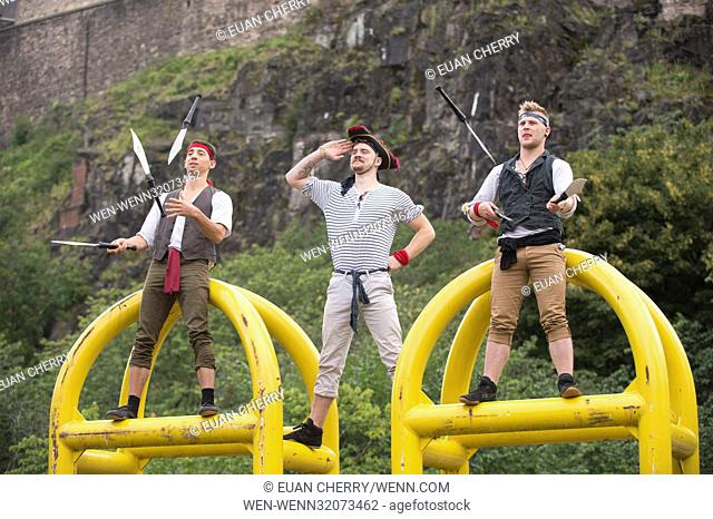 "Performers Fabian Galouÿe, Ronan Jenkinson, and Samuel Letch from """"Arr We There Yet!?"""" perform stunts on the anti terror barriers below Ediburgh Castle"