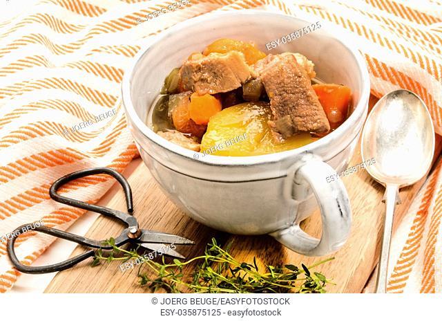 traditonal irish stew in a grey mug with thyme