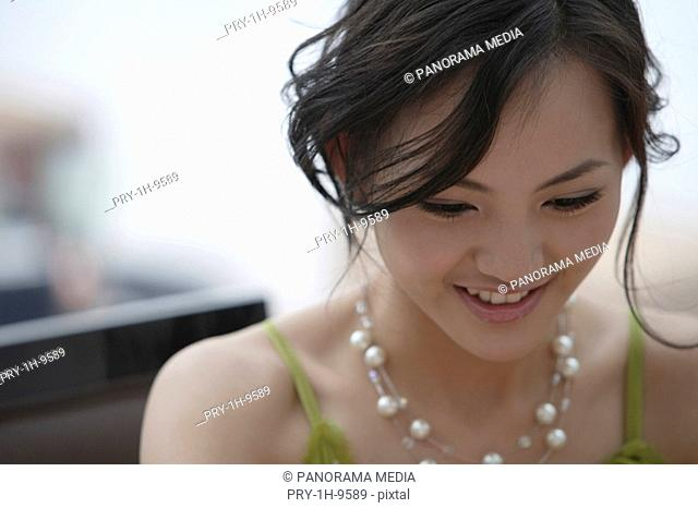 Close-up of a young woman wearing pearl necklace