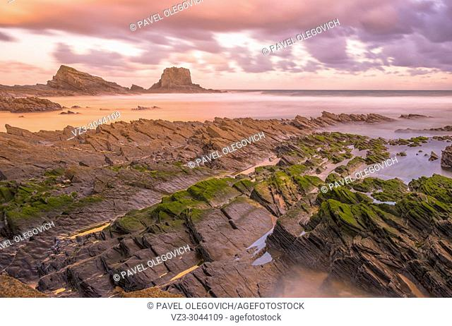Long exposure photography: View of Zambujeira do Mar beach at sunset in Costa Vicentina, Portugal