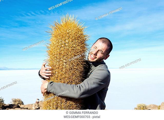 Bolivia, Atacama, Altiplano, Salar de Uyuni, man embracing cactus