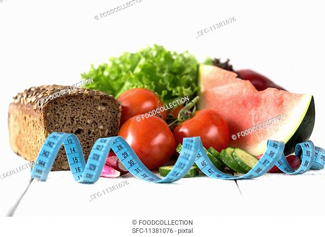 An arrangement of vegetables, lettuce, watermelon, wholemeal bread and a measuring tape