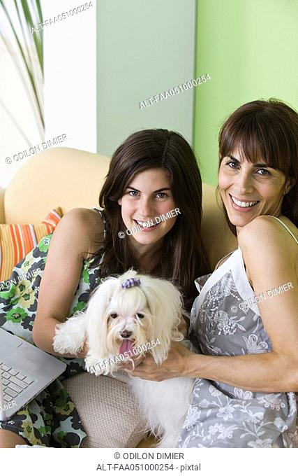 Mother and teen daughter with pet dog, portrait