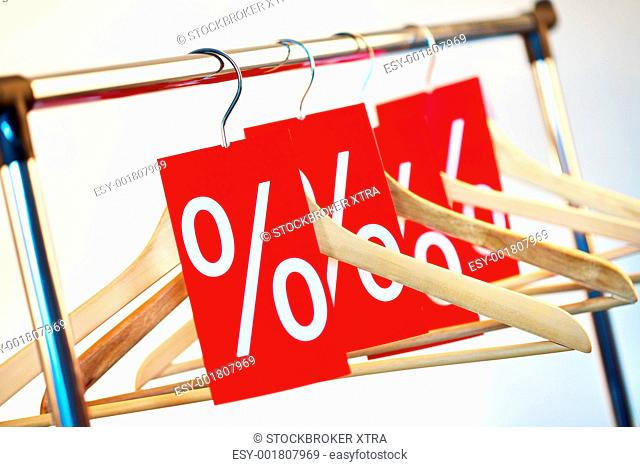 Image of several wooden hangers with red discount tags