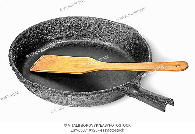 Old cast iron pan with wooden spatula isolated on white background