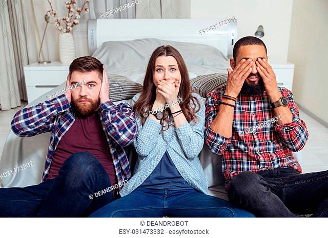 Three young friends sitting in see so evil, hear no evil, speak no evil poses at home