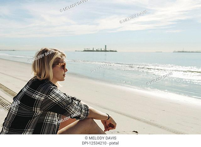 A woman sits on a beach looking out to the water; Long Beach, California, United States of America