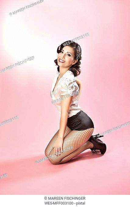 Woman in pin-up style posing on studio floor