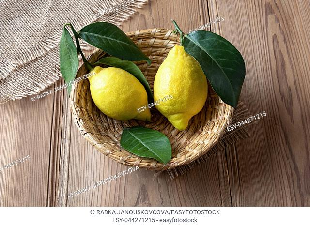 Two fresh lemons with leaves in a basket