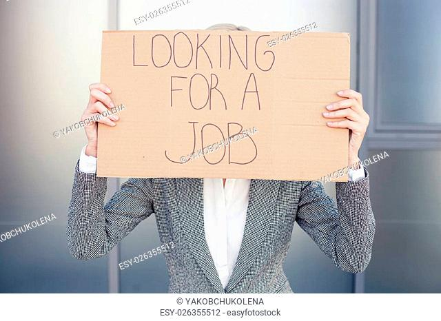 Pretty woman in formalwear is looking for a job. She is standing and holding a cardboard signboard. The lady is covering her face with it