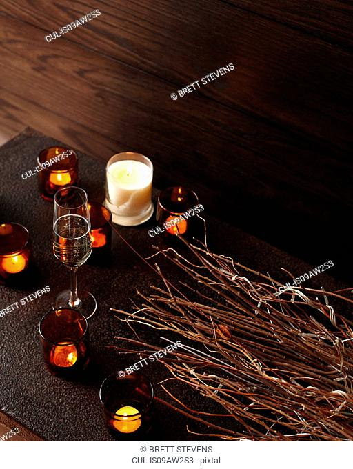 Lit candles and glasses of champagne on wooden table
