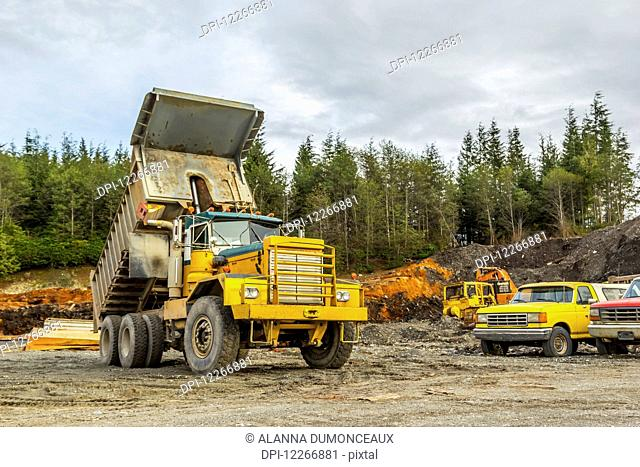 An old dump truck is positioned in a gravel yard with box raised up. Lumber and other equipment are shown in the background of the work yard against the forest;...