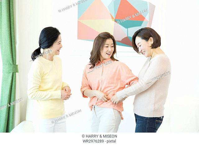 Three smiling middle aged women talking about diet