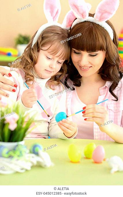 Portrait of a mother and daughter paint Easter eggs