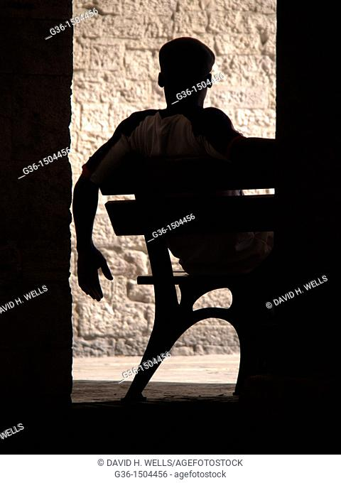 Man sits on bench in Todi, Perugia, Italy