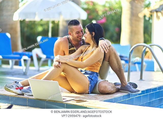 young couple laughing together while sitting with mobile laptop next to pool in holiday resort. Greek ethnicity. In Hersonissos, Crete, Greece