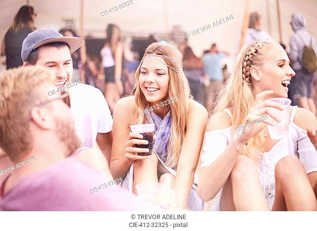Young friends hanging out drinking at music festival