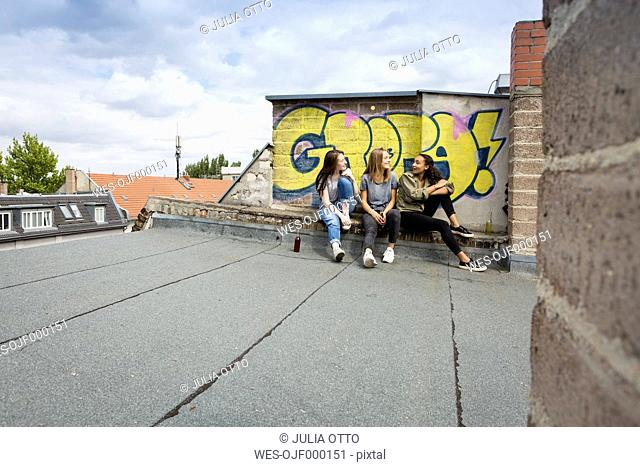 Three teenage girls sitting together on roof top