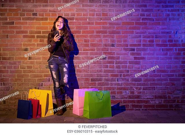 Pretty Mixed Race Young Adult Woman with Shopping Bags Using Her Cell Phone Against a Brick Wall - Plenty of Copy Space