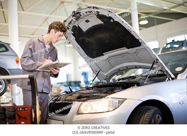 Mechanic examining car engine in garage