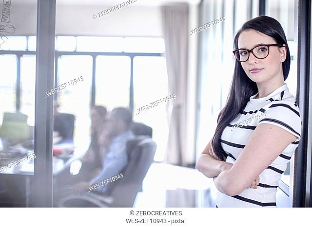 Businesswoman leaning against glass pane with her team in background