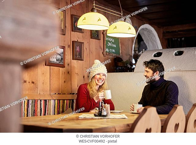 Happy couple drinking hot drink in rustic mountain hut