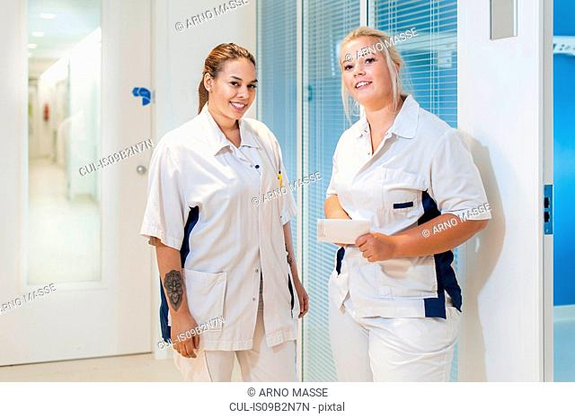 Nurses on hospital ward looking at camera smiling