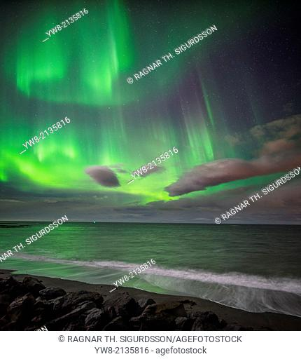 Aurora Borealis or Northern lights over waves breakiing on the beach in Seltjarnarnes, Reykjavik, Iceland