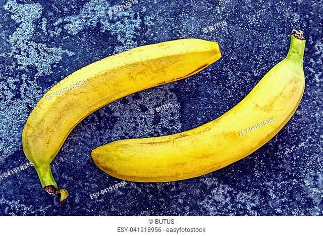 two ripe big yellow banana on gray ice on the street