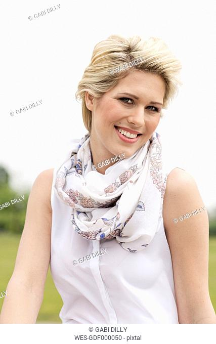 Germany, North Rhine Westphalia, Portrait of young woman, smiling, close up