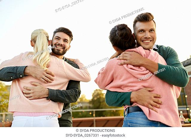 couples or friends hugging at on rooftop party