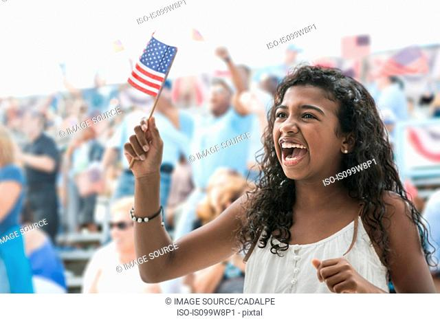 Girl cheering and waving american flag