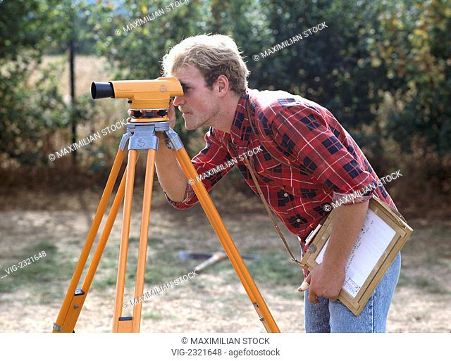 Engineer surveys a construction site with a theodolite, - 01/01/2010