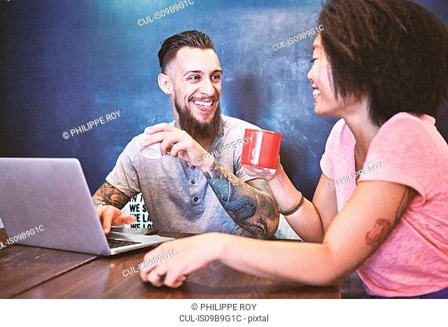 Multi ethnic hipster couple in cafe using laptop, Shanghai French Concession, Shanghai, China