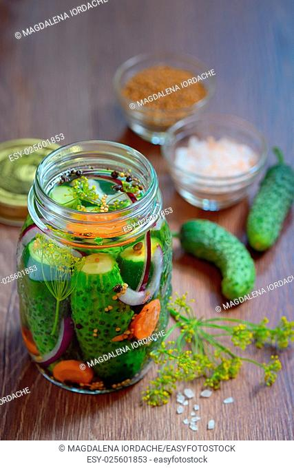 Pickled cucumbers, homemade preserved on wooden table