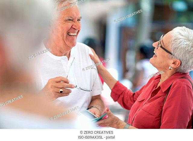 Senior man and mature woman chatting and laughing in city