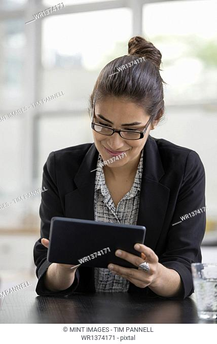 Young professionals at work. A woman wearing a black jacket, using a black digital tablet