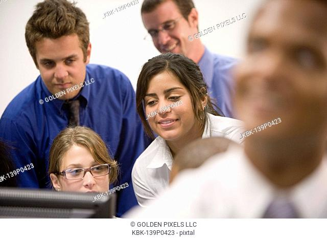 Office workers gathered around computer screen