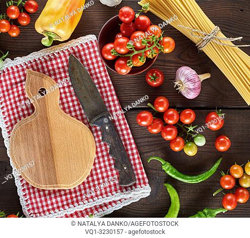 cutting board with a knife and fresh red cherry tomatoes, beside a tied bundle of long raw spaghetti