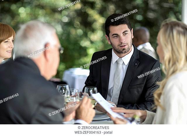 Elegant people at outside restaurant having a conversation