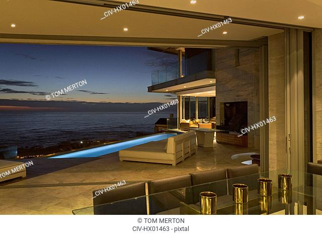 Illuminated home showcase patio with lap pool and twilight ocean view