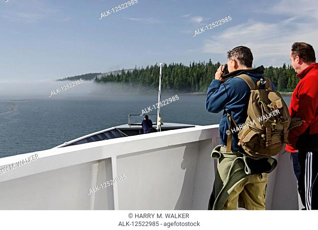 Two tourists watch as Alaska State Ferry approaches fog bank near the entrance of Sumner Strait from Wrangell Narrows, Southeast Alaska; Alaska