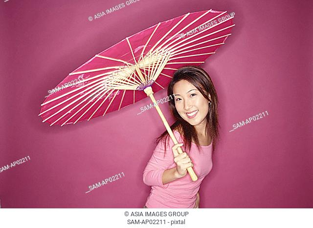 Woman with umbrella, standing against pink background